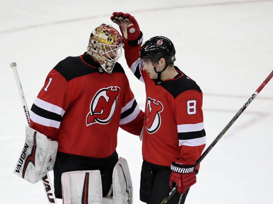New Jersey Devils goaltender Keith Kinkaid (1) and defenseman Will Butcher (8) celebrate after defeating the New York Rangers 5-2 in an NHL hockey game, Tuesday, April 3, 2018, in Newark, N.J. (AP Photo/Julio Cortez)