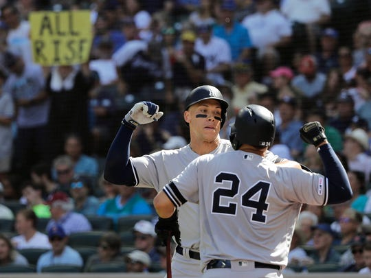 "A fan holds a sign that reads ""All Rise"" as New York Yankees' Aaron Judge, left, greets Gary Sanchez (24) after Judge hit a two-run home run against the Seattle Mariners during the fifth inning of a baseball game, Wednesday, Aug. 28, 2019, in Seattle. (AP Photo/Ted S. Warren)"