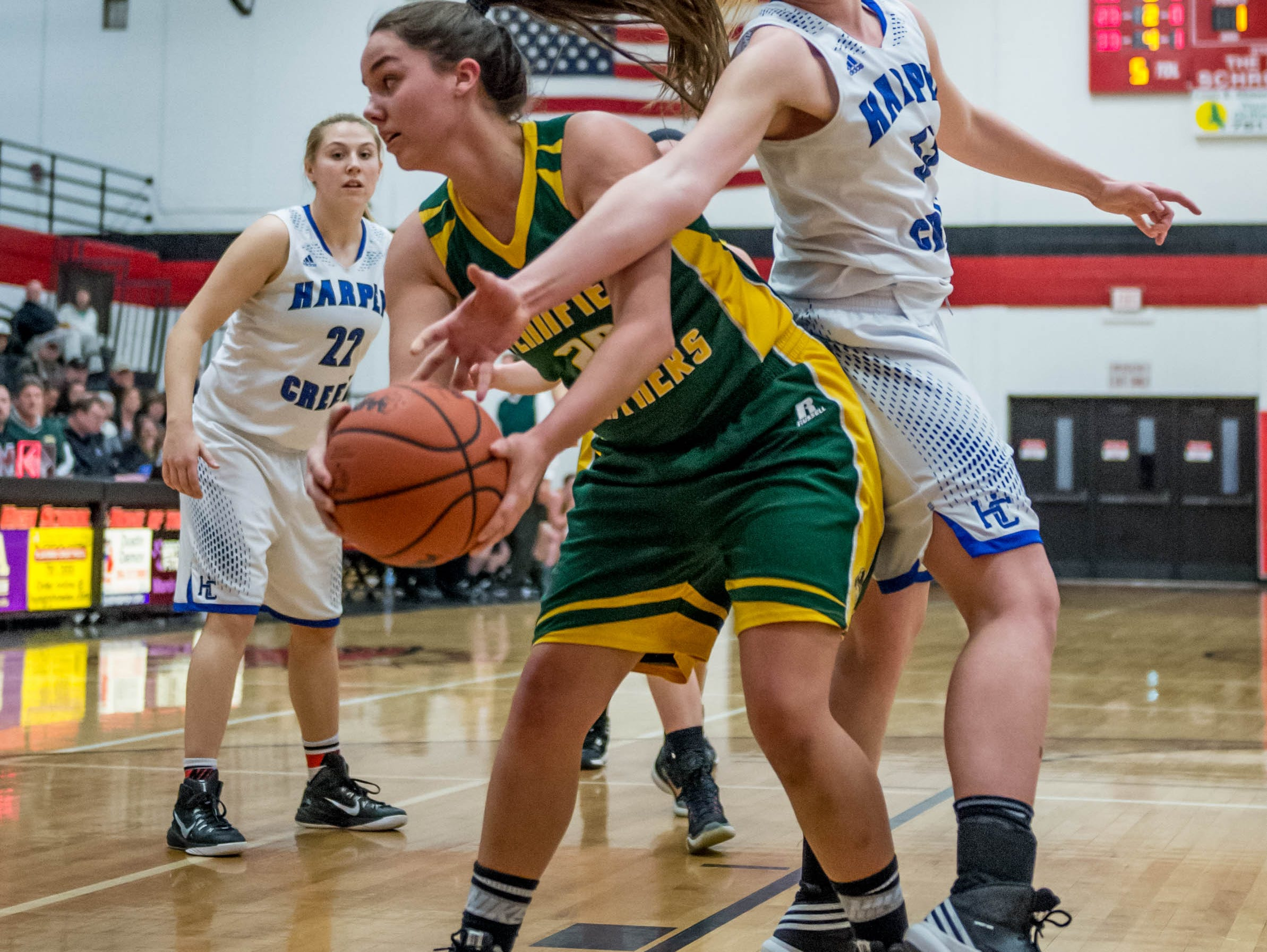 Harper Creek's Olivia Leson (33) goes for the ball from Pennfield's Brooke Lenz (20) in first round of districts game at Marshall Monday evening.