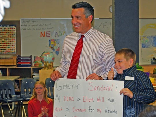 Nevada Gov. Brian Sandoval holds a poster given to him by 9-year-old Elliott Burgos, which Burgos had used on Facebook to invite the governor to his classroom at High Desert Montessori. Sandoval accepted and met with the Burgos and the class on Friday, Oct. 9.