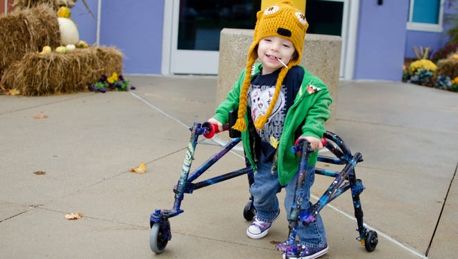 """Two-year-old Henri """"Kai"""" Grabill of Des Moines, who was born with hypotonia, walks with a custom-painted walker."""