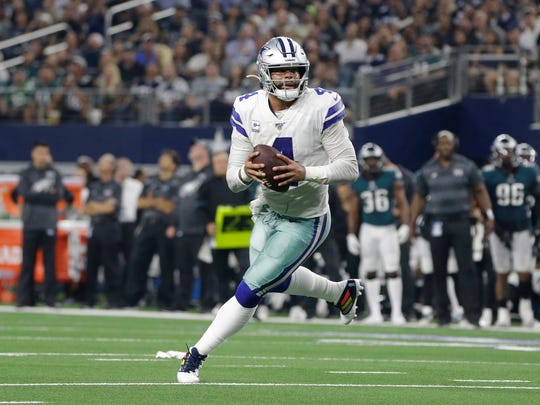 Oct 20, 2019; Arlington, TX, USA; Dallas Cowboys quarterback Dak Prescott (4) rolls out and throws a touchdown pass in the second quarter against the Philadelphia Eagles at AT&T Stadium. Mandatory Credit: Tim Heitman-USA TODAY Sports