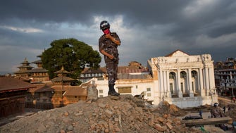 A Nepalese policeman stands on top of rubble April 26, 2015, at Basantapur Durbar Square.