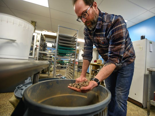 In this file photo taken on Dec. 30, 2015, Nathan Miller grabs a handful of Peru cocoa seeds in the kitchen of his Chambersburg store.