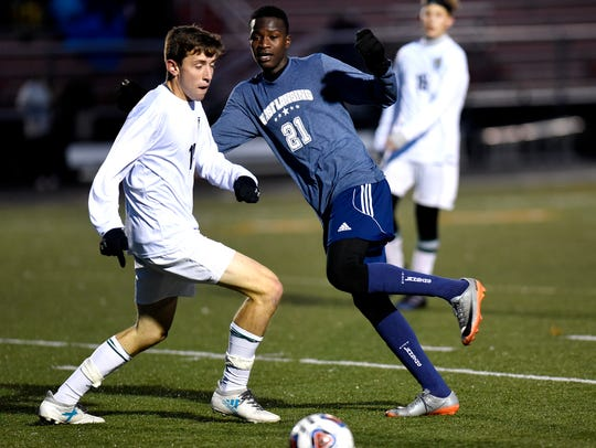 East Lansing's Mohamed Babale, right, kicks the ball