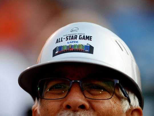 Wearing a commemorative helmet, a fan looks on in the