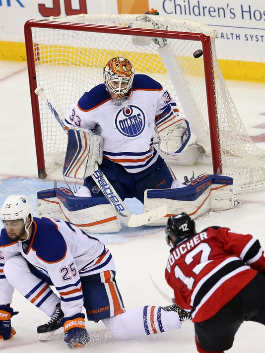 New Jersey Devils left wing Reid Boucher (12) shoots the puck past Edmonton Oilers goalie Cam Talbot (33) for a goal during the third  period of an NHL hockey game Tuesday, Feb. 9, 2016, in Newark, N.J. Devils won 2-1. (AP Photo/Mel Evans)