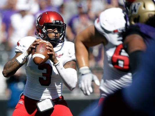 FILE - In this Sept. 6, 2014, file photo, Eastern Washington quarterback Vernon Adams Jr.,left, looks to throw against Washington during the second half of an NCAA football game in Seattle. Adams, one of the best players in FCS, is considering a transfer to Oregon, where he could replace Marcus Mariota next season. Graduate transfer quarterbacks often create a stir but while fans hope they're getting the next Russell Wilson there is no guarantee the next guy makes an impact. (AP Photo/Elaine Thompson, File)