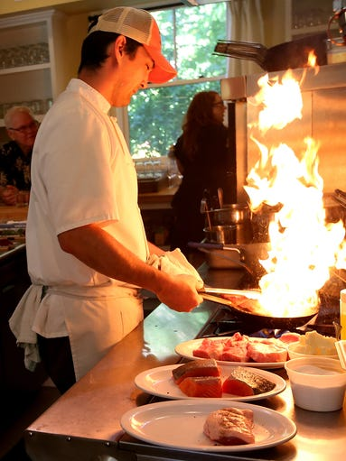 A pan flares up as Chef Tadao Mitsui cooks for the