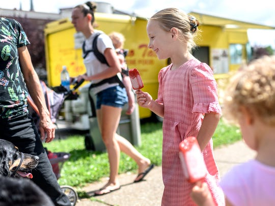 "Janae Stoll (center) enjoys a ""strawberry lemonade"" ice pop from Lollys Pop Bar during the Franklin Street Bazaar in Evansville, Ind., Saturday, June 23, 2018."