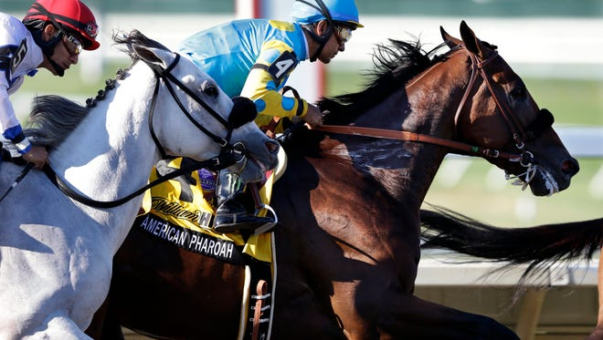 Jockey Victor Espinoza, right, on Triple Crown winner American Pharoah (4), leads Paco Lopez (5) on Mr. Jordan through the first turn during the Haskell Invitational horse race at Monmouth Park in Oceanport, N.J., Sunday, Aug. 2, 2015. American Pharoah won. Keen Ice  was second. (AP Photo/Mel Evans)