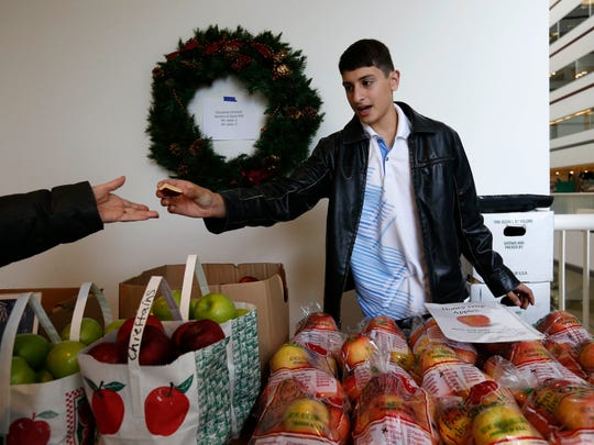 Hassan Younes, 14, offers a customer a taste of the Chieftain apples Friday, Nov. 20, 2015, that were grown on the Storybook Orchard in Story City during the Winter Farmers' Market in downtown Des Moines.
