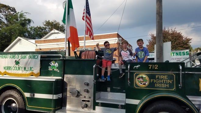Connor Leavy, Brendan Keown and Patrick Keown.sit on the Fire Fightin' Irish fire truck.