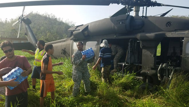 Ohio Army National Guar Pfc. Carlina Croston unloads supplies off a helicopter in Puerto Rico. The 137th Signal Company, which is based in Newark, spent a month on the island helping residents recover from Hurricane Maria.