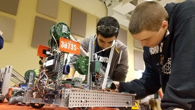 South Gibson County High School 10th grader Jeremiah Gonzalez and ninth grader Jacob Smith make some last minute adjustments to their robots before competing in the field at the inaugural Cupid's Challenge hosted by Hornets Robotics in Milan on Fe. 10, 2018.