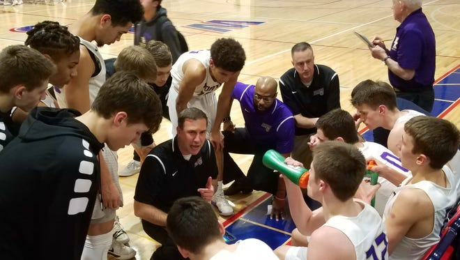 North Kitsap boys basketball coach Scott Orness draws up a play during Thursday's district semifinal game against Renton.