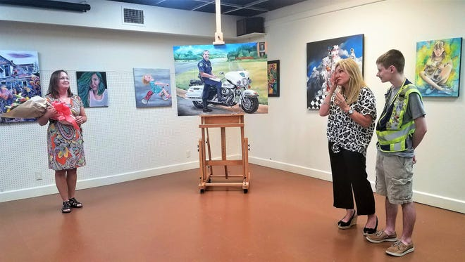 Artist Kina Tiemann, Annemarie Holder, and Kyler Holder accept the gift of a painting honoring Abilene policeman Rodney Holder, who died in April 2010. Family, friends, and first responders attended a ceremony Tuesday afternoon unveiling the painting.