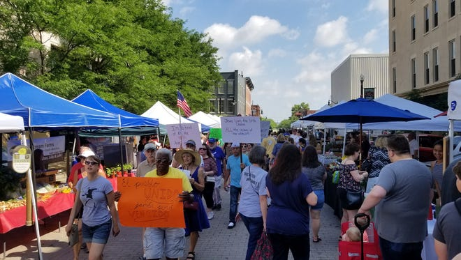 Hundreds marched through Lafayette Farmer's Market in support of immigrants Saturday, June 30.
