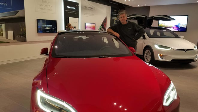 Detroit News auto critic Henry Payne poses with a $75,000 base price Model S sedan at the company's gallery store in Troy's Somerset mall. Somerset does not yet have a Model 3 on display as most copies are going to customers to met a 450,000 order backlog.
