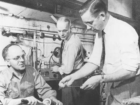 "Dr. Roy Plunkett shows his assistant, Jack Rebok (left) the white powdery material he scraped from inside the cylinder they curiously sawed open after a ""failed"" experiment with refrigeration gases. Bob McHairness looks on during this reenactment of the 1938 discovery."""