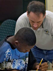 In this 2008 photo, science teacher Scott Guisbert helps a student in preparation for FCAT.