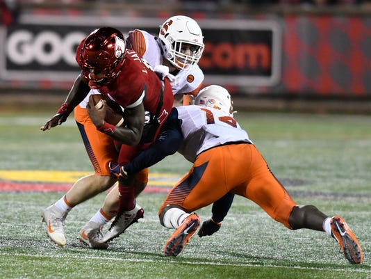 Louisville quarterback Lamar Jackson (8) is brought down by Syracuse defensive back Evan Foster (14) and linebacker Ryan Guthrie (41) during the first half of an NCAA college football game, Saturday, Nov. 18, 2017, in Louisville, Ky. (AP Photo/Timothy D. Easley)