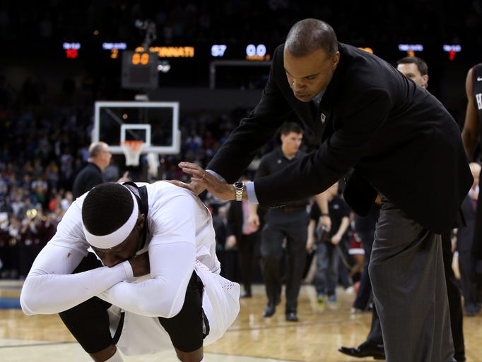A dejected Justin Jackson (5) kneels on the floor as Harvard coach Tommy Amaker offers his condolences.