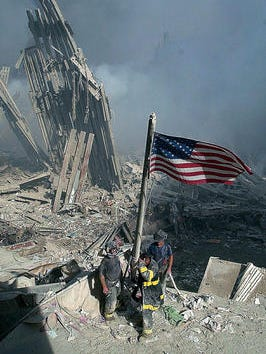 Three New York City firefighters raise the American flag from the rubble of the World Trade Center, Sept. 11, 2001.
