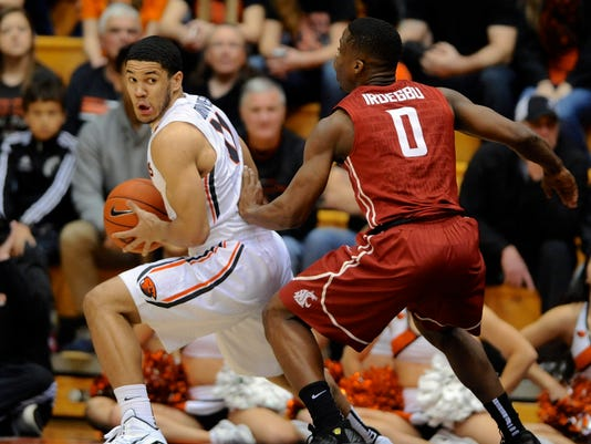Washington State's Ike Iroegbu (0) defends against Oregon State's Malcolm Duvivier (11) during the first half of an NCAA college basketball game in Corvallis, Ore., Thursday, Feb. 5, 2015.  (AP Photo/Greg Wahl-Stephens)