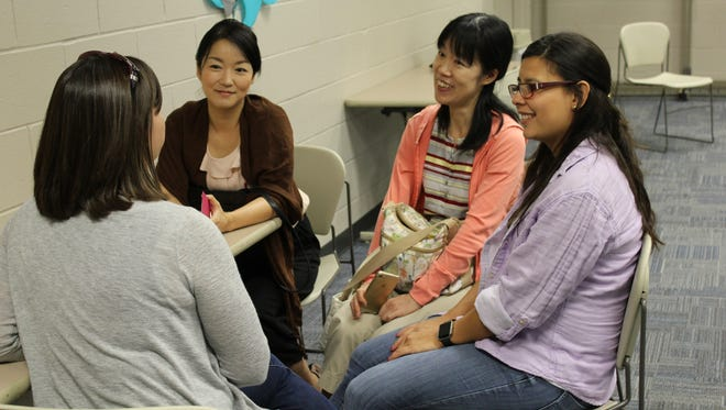 Members of the Northern Kentucky English Conversation Club meet every week to improve their knowledge of American culture and the quirks of the English language. Seen here are, from left, Keiko (Japan), Mayumi (Japan), Natalia (Mexico) and Emily (back to picture), a native English speaker who volunteers to help guide the discussions.