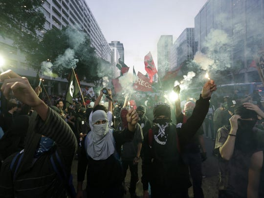 Students wearing masks burn flares during a protest demanding better education and protesting the money spent on the Olympics in Rio de Janeiro, Brazil, Wednesday, July 6, 2016. With the Olympics set to start on Aug. 5, the games and the city have been overshadowed by security threats, violence, the Zika virus and a national political corruption scandal. (AP Photo/Silvia Izquierdo)