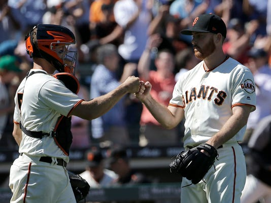 San Francisco Giants catcher Nick Hundley, left, and pitcher Sam Dyson celebrate after beating the Cleveland Indians in a baseball game in San Francisco, Wednesday, July 19, 2017. The Giants won 5-4. (AP Photo/Jeff Chiu)