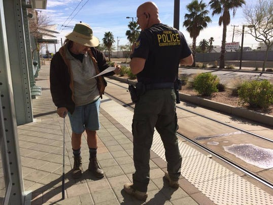 Phoenix police officer hands flier to commuter on Valley Metro light rail platform