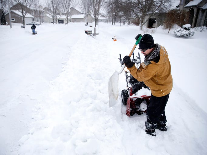 Rob Riley, of Appleton, uses a shovel to break down