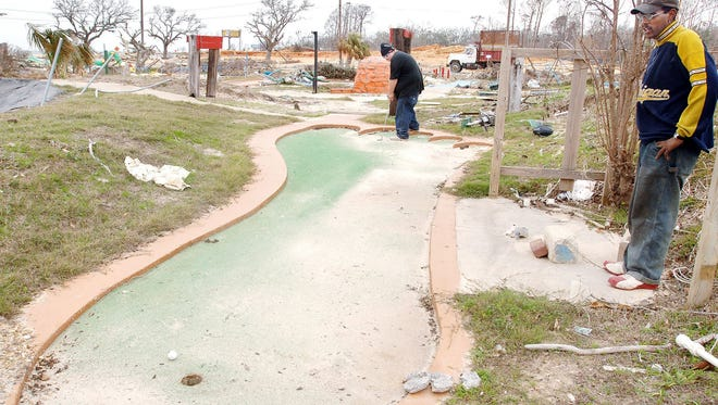Former employees play the Bigfoot hole at what remains of the mini-golf course at Funtime USA on U.S. 90 in Gulfport in 2006. The theme park,  destroyed by Hurricane Katrina in 2005, is returning.