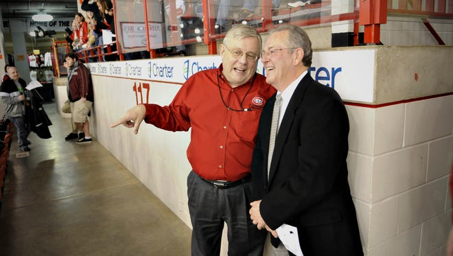 St. Cloud State University President Earl Potter (left) talks with Gino Gasparini during a game against Wisconsin at the National Hockey Center in St. Cloud in 2011.