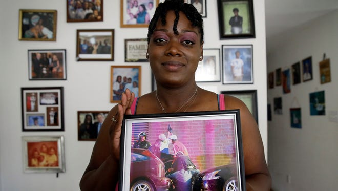 In this June 30, 2017, photo, Shetamia Taylor holds a picture that hangs on her living room wall in Garland, Texas, that shows first responders assisting Taylor after she was shot during a Black Lives Matter protest in downtown Dallas on July 7, 2016.