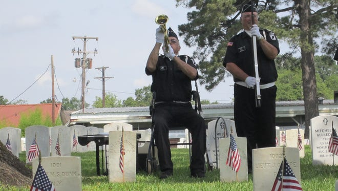 Perry L. Fleming, commander of the Alexandria-Pineville Veterans Honor Guard, plays taps at the end of the Memorial Day ceremony on Monday at the Alexandria National Cemetery.