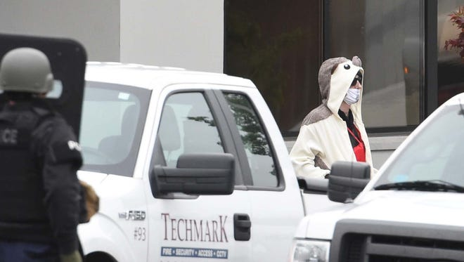 A man wearing a full animal costume and surgical mask walks out of a TV station in Baltimore on April 28, 2016. Baltimore police say a department sniper shot the man, who police say walked into a TV station displaying what appeared to be an explosive device on his chest. (Kenneth K. Lam/The Baltimore Sun via AP)  WASHINGTON EXAMINER OUT; MANDATORY CREDIT   ORG XMIT: MDBAE201