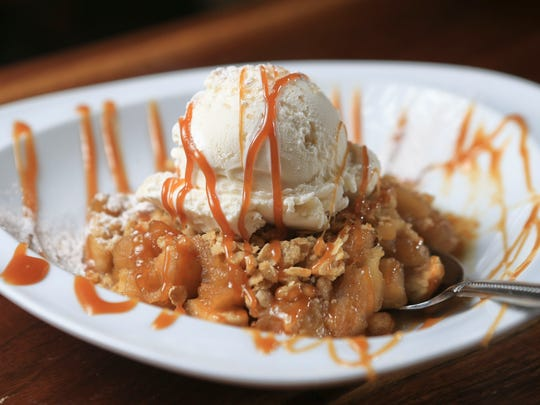 Village Anchor's Huber's Winesap apple crisp includes bourbon-apple cider caramel, with Comfy Cow vanilla bean idea cream and Bourbon Barrel sea salt.