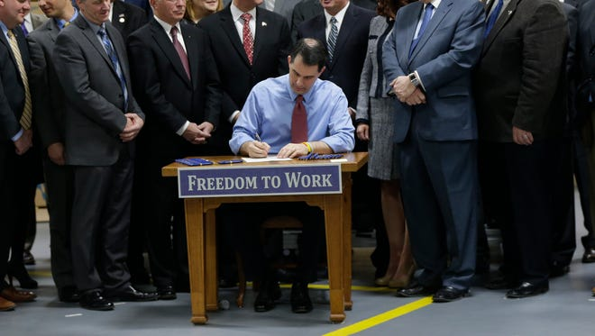 Wisconsin Gov. Scott Walker signs a right-to-work bill into law at Badger Meter in Brown Deer on Monday morning.  The new law, which takes effect immediately, makes Wisconsin the 25th right-to-work state and the first to do it since Michigan and Indiana in 2012.