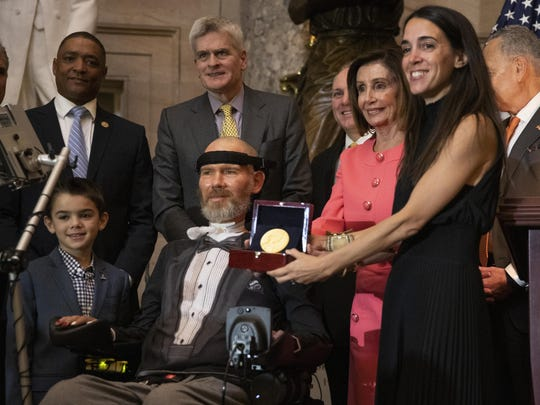 A Congressional Gold Medal is presented to Steve Gleason Wednesday in Washington. Holding the medal is his wife, Michel Gleason.