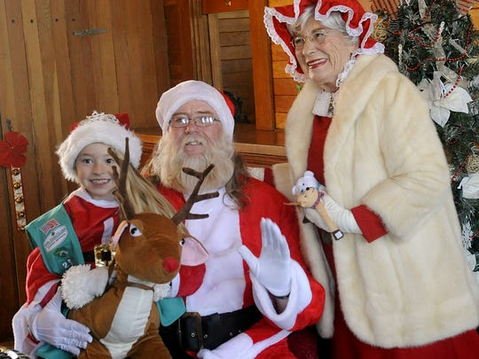 Alina Williams, 9, has her photo taken with Santa and Mrs. Claus.