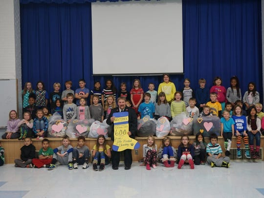 During an all-school assembly, third-grade students from John Marshall Elementary School present Lt. Jacob Tripp of The Salvation Army with more than 600 items to help keep the community's homeless warm. The students doubled their goal of collecting 300 items during their Socktober campaign.