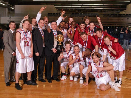 Jon Horst (warmup jacket, smiling  in middle) celebrates with his Rochester College teammates after winning a USCAA championship.