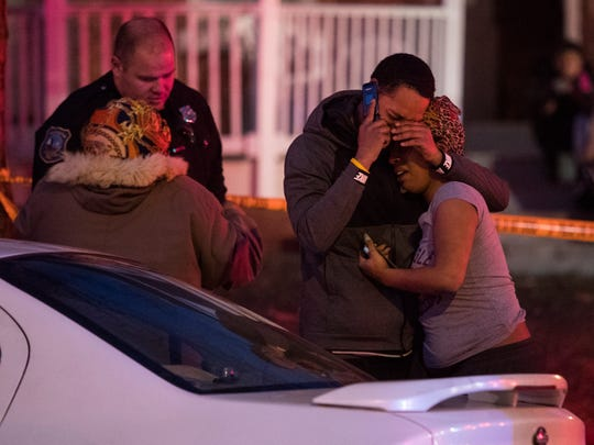 People comfort each other outside a house fire in the
