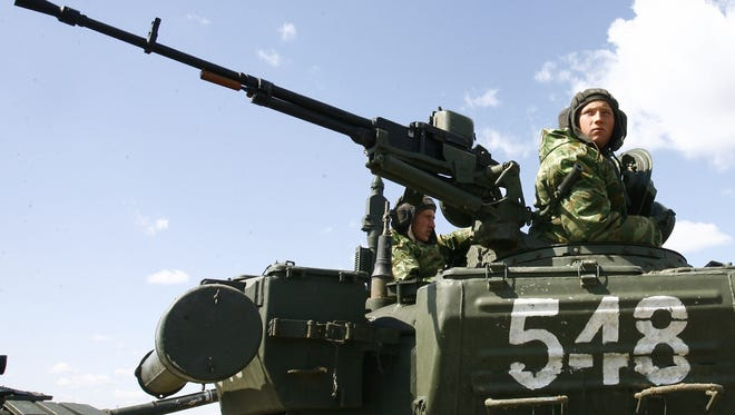 Russian soldiers sit atop their tank during military exercises in the southern Russia's Volgograd region, on April 3, 2014.