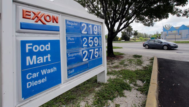 A, a motorist drives by an Exxon sign displaying gas prices in Opa-locka, Fla., on July 19, 2017.