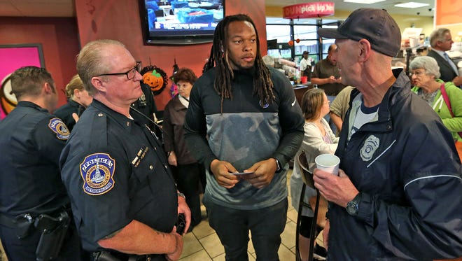 IMPD's Greg Scott, left, and John Wall, right, talk with Indianapolis Colts playerJabaal Sheard during Coffee with Colts & Cops at Dunkin Donuts, Tuesday, Oct. 10, 2017.