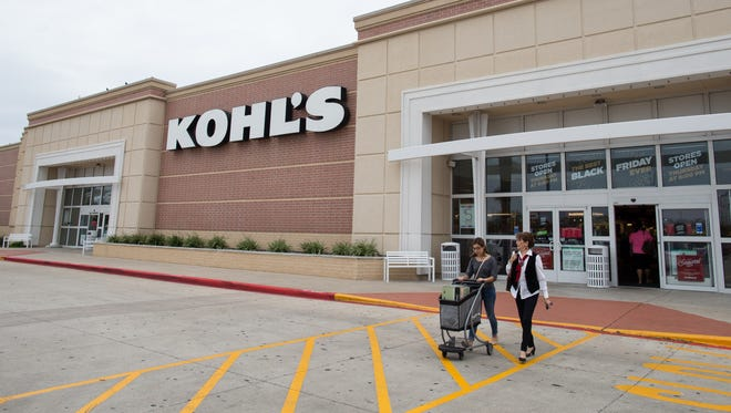 Shoppers push a cart of items as they leave Kohl's on Friday morning, Nov. 27, 2015, in Corpus Christi, Texas.